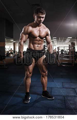 Athlete Muscular Bodybuilder Man Posing With Dumbbells In Gym