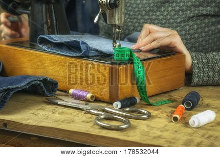 Woman working on an old sewing machine. The concept of home production and repair of clothing.