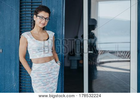 Portrait Of  Fashion Smiling Positive Young Smart Woman In Glasses On Blue Background