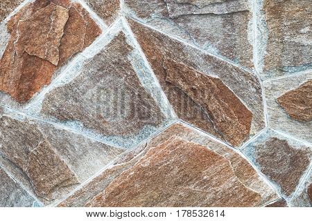 Stonework with asymmetry. Close-up bright vintage bricks wall background. stone wall for background texture. Closeup view of stone wall.