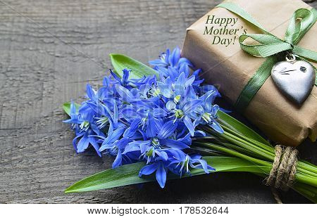 Bouquet of Blue Scilla (Squill) flowers and gift box with vintage silver heart on old wooden table.Happy Mother's Day decoration.Spring flowers for Mother's Day.Selective focus.
