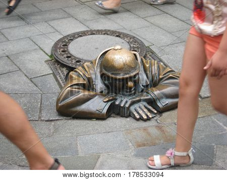 """Cumil the sewer worker statue in Bratislava Slovakia. The unusual modern artwork """"Man at work"""" on the busy city center street, coming from the ground."""