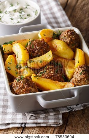 Meat Balls With Potato Wedges In A Baking Dish And Sour Cream Close-up. Vertical
