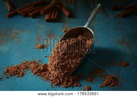 Metal scoop with cocoa powder on color background