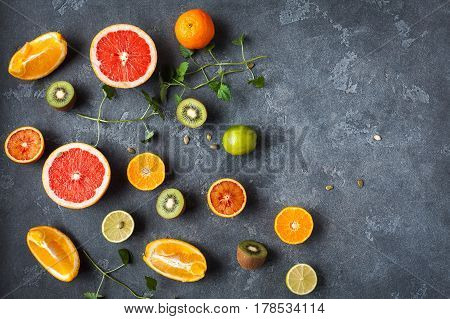 Fruit background. Colorful fresh fruit on dark table. Orange tangerine lime kiwi grapefruit. Flat lay top view