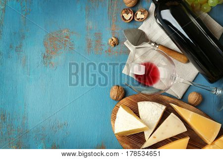 Composition of delicious cheese, nuts and wine on blue textured table