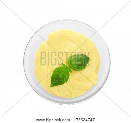 Creamy cheese and basil leaves in glass bowl, isolated on white