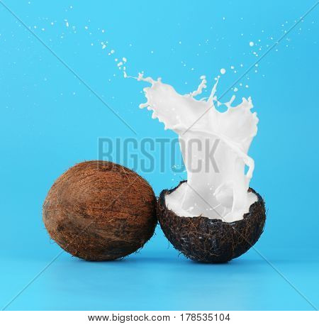 Coconuts with splashes of milk on color background