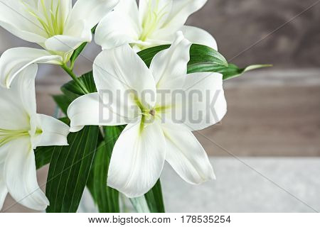 Beautiful white lilies on blurred background, closeup