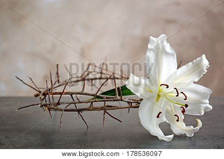 Crown of thorns and white lily on beige background