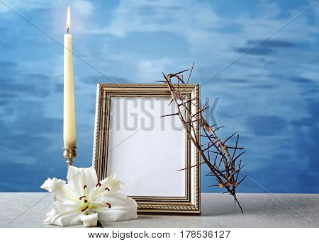 Photo frame, crown of thorns, lily and candle on light background
