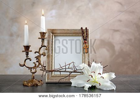 Crown of thorns, lily, candles and photo frame with rosary on beige background