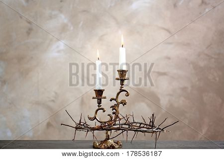 Crown of thorns and candles on beige background