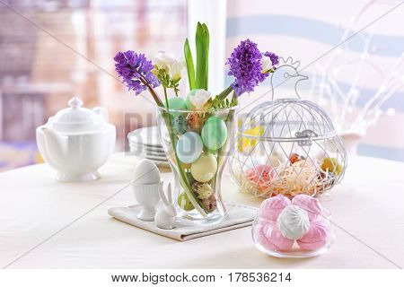 Beautiful Easter pastel decorations with table setting on blurred background