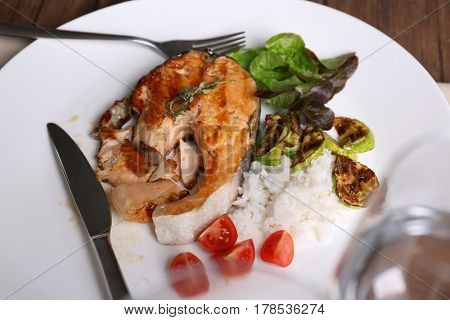 Plate with grilled salmon steak, vegetables and rice on dinning table