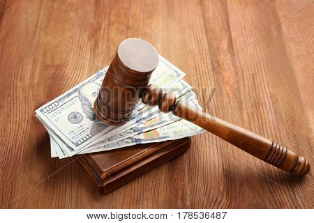 Judge's gavel and dollar banknotes on wooden background
