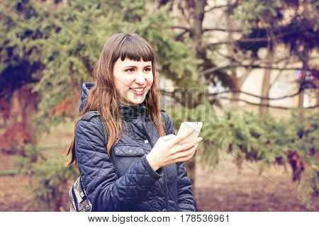Beautiful young girl reads messages in a mobile phone in a city spring park.