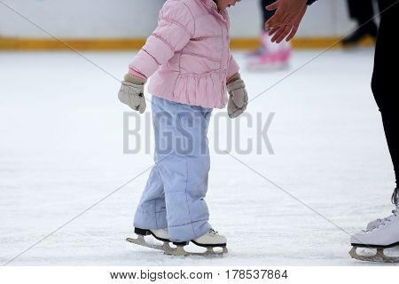 the girl helps the child to skate