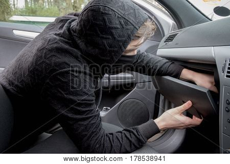 Masked teenage criminal stealing from a car