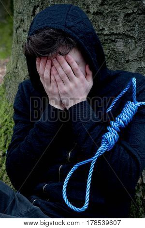Depressed teenage boy with a hangman's noose