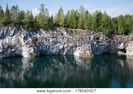 Steep coast of the Marble canyon in the sunny August afternoon. Mountain park of Ruskeal, Karelia