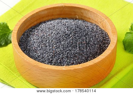 black poppy seeds in wooden bowl on green placemat