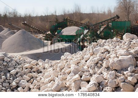 Pile of gravel-rock to be treated. Blurred on background machinery of a gravel pit.