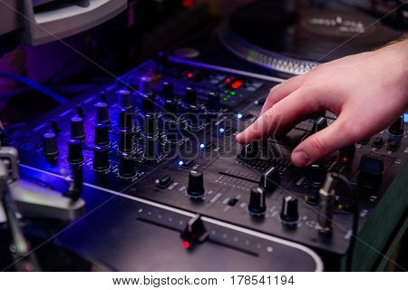 Close Up Dj Hands On Equipment Deck And Mixer With Vinyl Record At Party