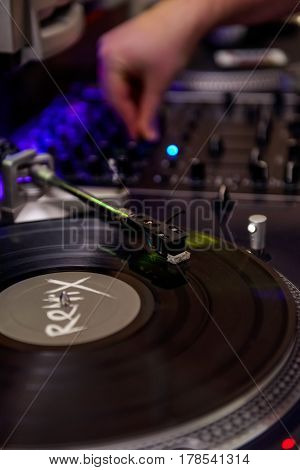 Close Up Turntable Playing Vinyl With Needle On The Record And Playing Dj On The Background. Selecti