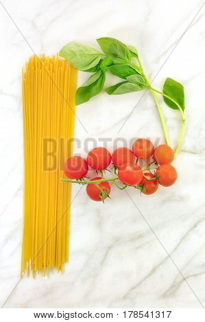 An overhead photo of a letter P for pasta, formed by spaghetti, cherry tomatoes, and a sprig of basil leaves, on a white marble background texture with copy space