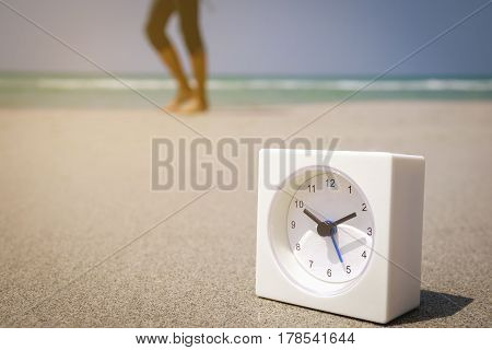Abstract white alarm clock on blue sea with nature background blur background vacation and holiday concept with copy space