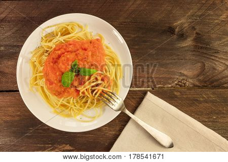 An overhead photo of a plate of spaghetti with a fresh homemade tomato sauce, and a place for text