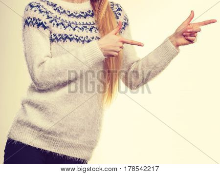 Winter fashion outfit ideas concept. Woman legs in black leggings trousers and grey furry jumper pointing right.