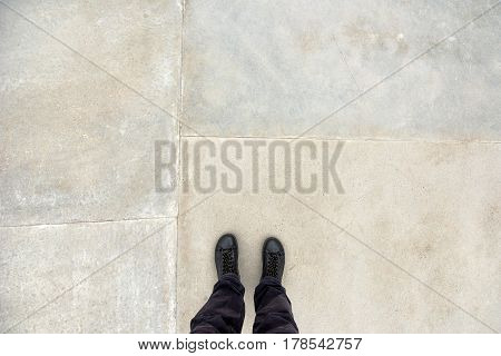 Man standing on concrete flooring surface feet in leather winter shoes from above copy space for quotation or graphic