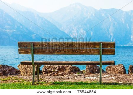 Wooden bench at coast of picturesque lake with blue mountain summits on background. Summer scenic landscape. Calmness, silence and harmony concept.