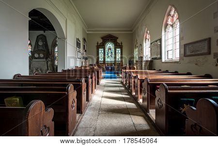 CAMBRIDGESHIRE, UK - 11 MARCH 2017: The interior of an old rural English church with its original wooden pews and altar.