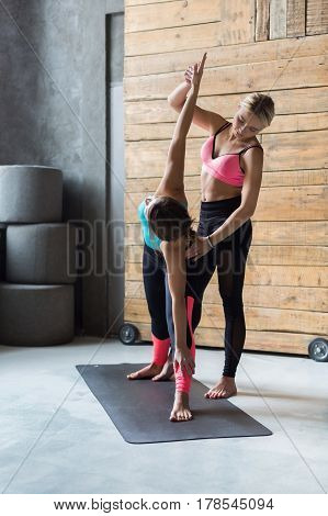 Yoga class instructor helps beginner to make asana exercises. Teacher assists to make triangle pose, trikonasana. Healthy lifestyle in fitness club. Stretching with coach