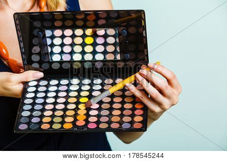 Cosmetic beauty procedures and makeover concept. Woman holds makeup professional eye shadows palette and brush. Make up applying.