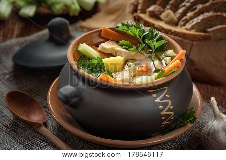 soup in the pot bread wooden spoon on the table closeup