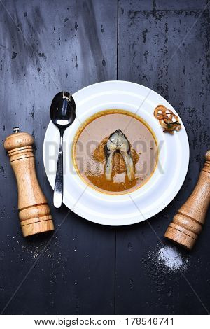 Cream Soup Brown Color With Fish, Pepperbox, Saltcellar And Spoon