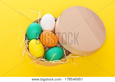 Painted Easter Colorful Eggs In Wooden Box On Yellow Background