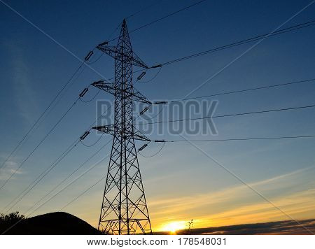 Electric tower backlit at sunrise, view from below