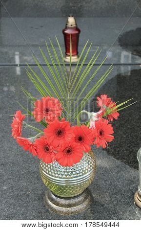 red gerbera flowers and green leaf arranged in the vase on the grave