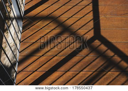 Photo of sunshine to the balcony and reflection the shadow on wooden floor