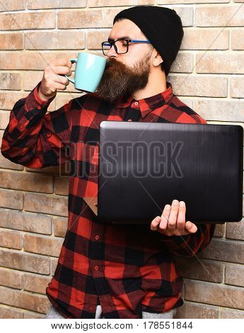 Bearded Brutal Caucasian Hipster Holding Laptop With Cup