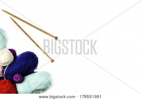 Knitting background frame. Pair of wooden knitting needles and colorful yarn on white background. Top view