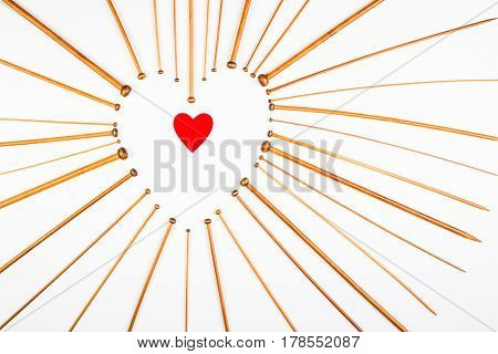 Heart symbol made of knitting needles on white background. flat lay, top view