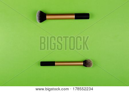Two make up brushes on greenery background. Top view.