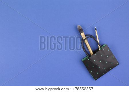 Make up brushes with black polka dot paper shopping bag on blue background. Top view. Flat lay.