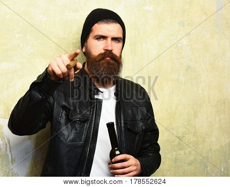 Bearded Brutal Caucasian Hipster Holding Bottle And Smoking Cigar